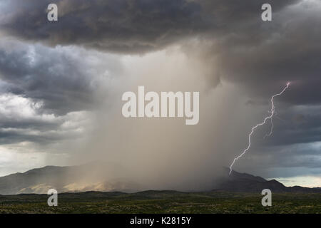 Thunderstorm with dark clouds, heavy rain and lightning over the Rincon Mountains near Tucson, Arizona Stock Photo