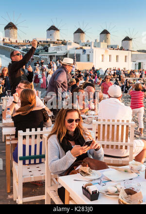 Tourists sitting at a waterfront cafe with the Kato Mili windmills behind them, Mykonos, Greece. - Stock Photo