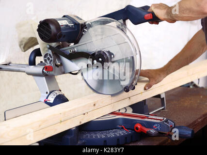 Closeup of hands of a person cutting wood lumber with a mitre saw, miter saw, circular blade. - Stock Photo