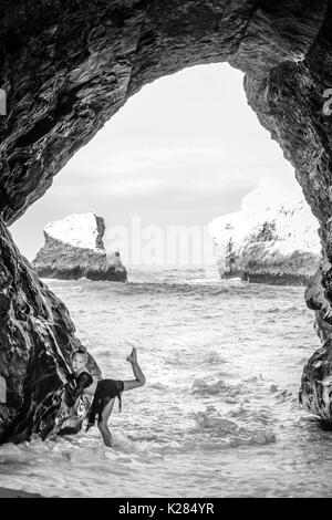 Small dancer posing in cave - Stock Photo