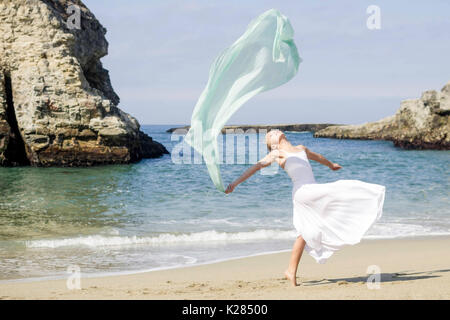 Dancer with scarf on beach - Stock Photo