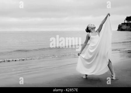Small dancer strikes a pose on beach - Stock Photo