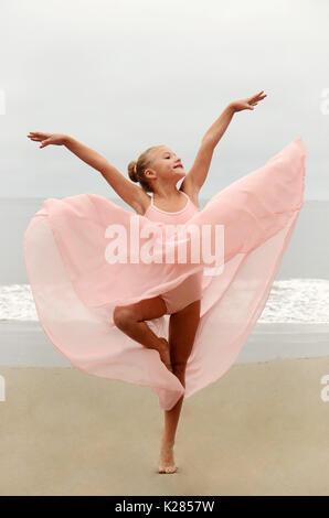 Dancer in flowy skirt on beach - Stock Photo