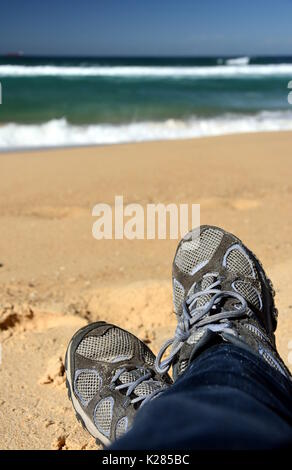 Crossed legs of woman relaxing on sandy beach, casual young person wearing sneakers sitting by the sea, selective - Stock Photo