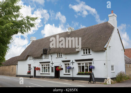 White painted thatched country pub / B & B, Rose and Crown under blue sky in English country village of Longburton, - Stock Photo