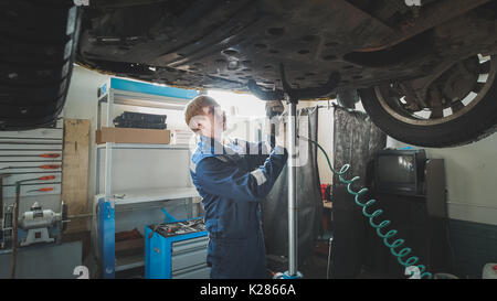 Worker Mechanic unscrewing parts of automobile's bottom under lifted car - Stock Photo