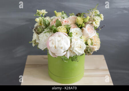 Beautiful tender bouquet of flowers in green box on gray background with space for text - Stock Photo