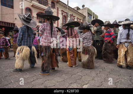 June 25, 2017 Cotacachi, Ecuador: children wearing sombreros and chaps athe the Inti Raymi celebrations - Stock Photo