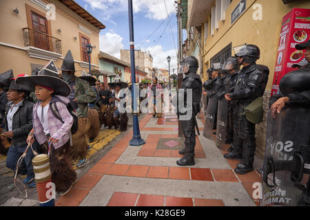 June 25, 2017 Cotacachi, Ecuador: riot police standing by as the male dances run down the street towards the main - Stock Photo