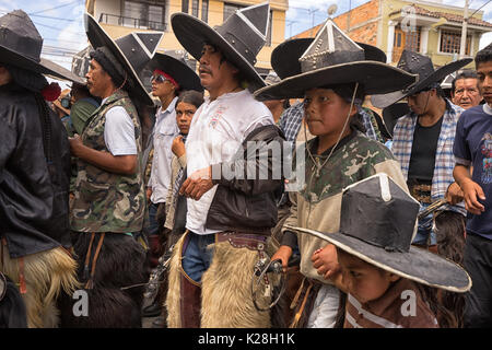 June 25, 2017 Cotacachi, Ecuador: kechwa indigenous men participating at the Inti Raymi parade in a tight formation - Stock Photo