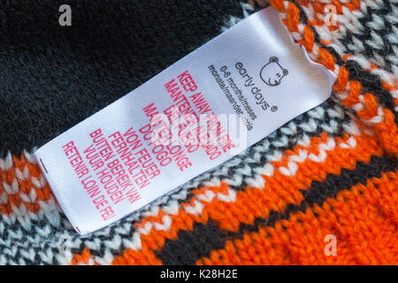Keep away from fire in many different languages on label in early days baby's hat for 0-6 months - multiple languages - Stock Photo