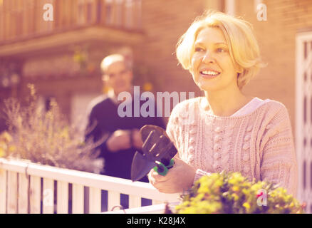 Joyful smiling mature woman with horticultural sundry and aged man drinking tea in patio - Stock Photo