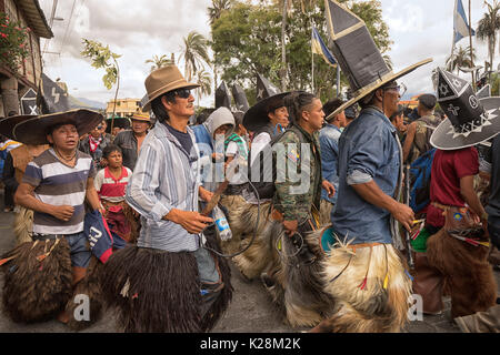 June 25, 2017 Cotacachi, Ecuador: indigenous quechua men wearing sombreros and chaps dancing at the Inti Raymi celebrations - Stock Photo