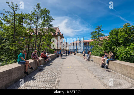 Bamberg, Germany - May 22, 2016: People seating and passing by bridge in downtown of Bamberg, Upper Franconia, Bavaria, - Stock Photo