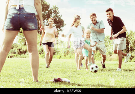 Family with four kids playfully running after ball outdoors on green lawn in park - Stock Photo