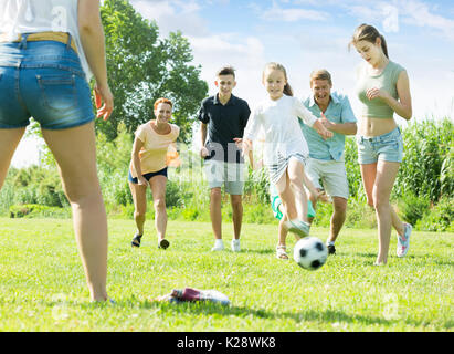 Happy family with four kids playfully running after ball outdoors on green lawn in park. Focus on teenager girl - Stock Photo