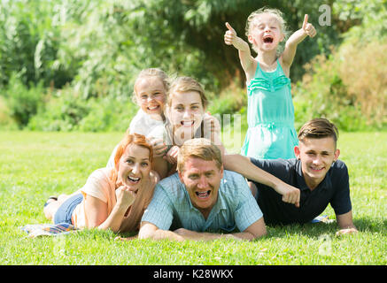 Adult man and woman with four kids lying in park on summer day - Stock Photo