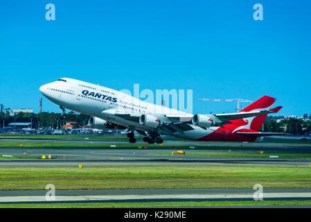 Qantas 747 jumbo jet taking off at Sydney International Airport, New South Wales, Australia. - Stock Photo