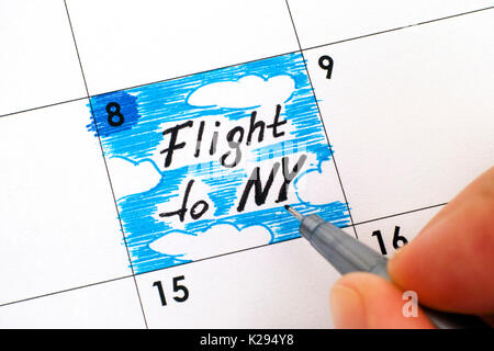 Woman fingers with pen writing reminder Flight to NY in calendar. Close-up. - Stock Photo