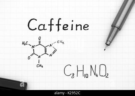 Chemical formula of Caffeine with black pen. Close-up. - Stock Photo