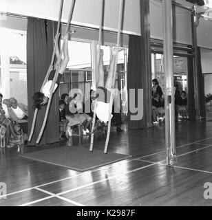 1960s, historical, picture shows two school girl gymnasts in tradittional PE kit performing an artistic routine - Stock Photo