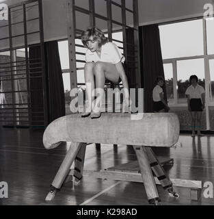 1960, historical, picture shows a young girl in a secondary school jumping or vaulting in barefeet over a suede - Stock Photo