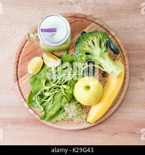 Fresh green vegetables and green smoothie in jar. Detox, diet or healthy food concept. Mason jar of dietary drink - Stock Photo