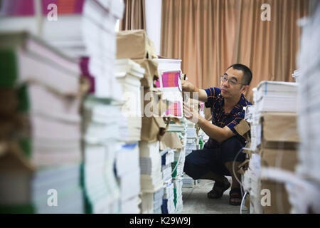 Chongqing, China. 29th Aug, 2017. A teacher arranges books at a classroom at Jianshan Middle School in Chongqing, - Stock Photo