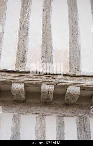 Lavenham Suffolk, detail of medieval lime-washed oak beams on the jettied front of the Guildhall in Lavenham, Suffolk. - Stock Photo