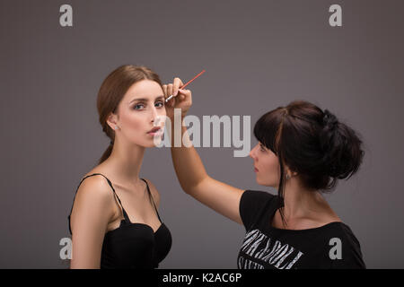 Makeup artist doing makeup for models for a photo shoot - Stock Photo