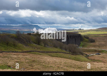 Iconic steam locomotive LNER class A3 60103 Flying Scotsman, travels over the Ribblehead Viaduct, Pen-y-Ghent beyond - Stock Photo