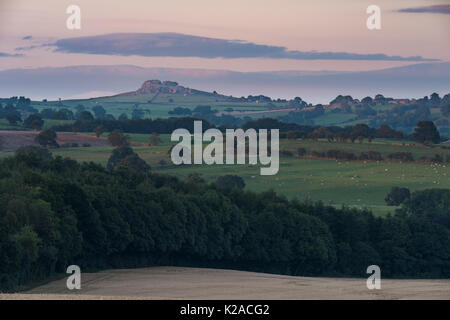 View under pink sky at sunset & across rolling farmland fields, of Almscliffe Crag, a distinctive high rocky outcrop - Stock Photo