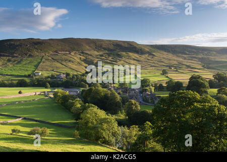 High view over beautiful, sunny Yorkshire Dales village of Burnsall in valley by River Wharfe & with steep, green, - Stock Photo