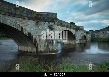 Scenic view of bridge spanning River Wharfe flowing gently through Burnsall village, on summer evening with blue - Stock Photo