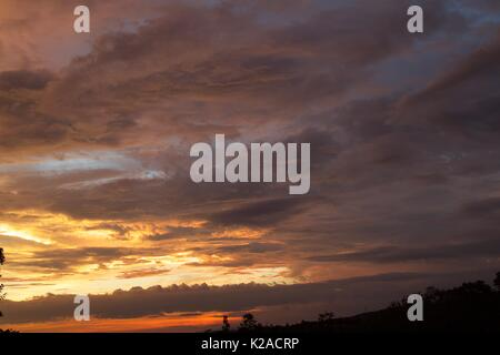beautiful images captured of amber coloured evening sky with sunset and clouds - Stock Photo