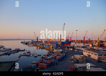 Port terminal with cranes, ships and containers near Salerno at dawn - Stock Photo