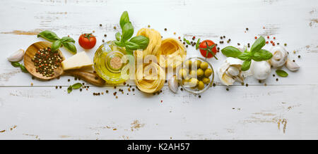 Italian food or ingredients background with fresh vegetables, pasta, cheese parmesan and spices. Top view - Stock Photo