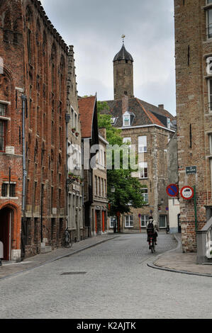 A cyclist rides down a quiet, narrow side street in the medieval city of Brugge / Bruges in West Flanders, Belgium - Stock Photo