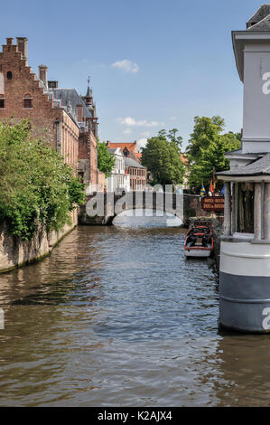 Tourists on a bridge over a quiet narrow canal with moored boat in the medieval West Flanders city of Brugge / Bruges - Stock Photo