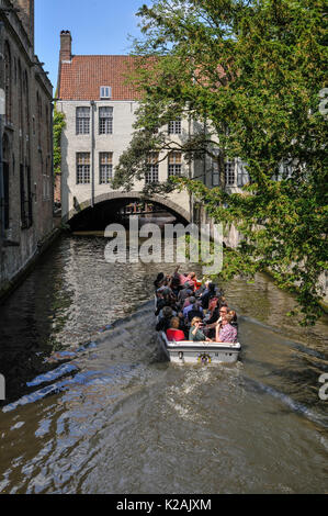 Tourists on a boat trip of the canals in the medieval city of Brugge / Bruges in West Flanders in Belgium - Stock Photo