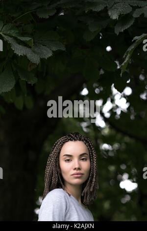 A beautiful girl with afro pigtails seriously looks at the camera on a background of green foliage of trees. - Stock Photo