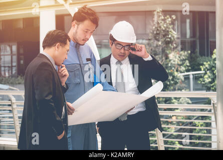 Team of architects and engineer at outdoor building and talking to planning work - Stock Photo