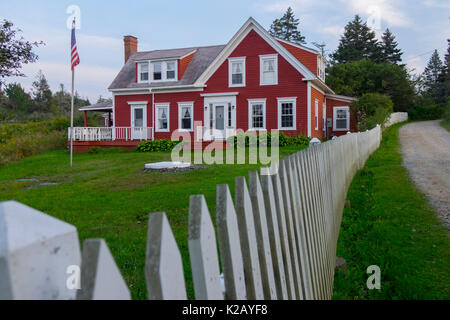 USA Maine ME Monhegan Island A red house on Lobster Cover Road with a white picket fence - Stock Photo