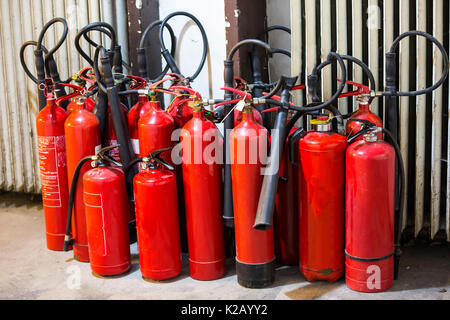 Many red fire extinguishers on the ground. Foam, Carbon dioxide, Powder and Water. - Stock Photo
