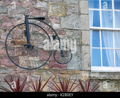 Old fashioned penny farthing bicycle model featured on stone wall of Greyfriar's Bobby pub, Candlemaker Row, Edinburgh, - Stock Photo