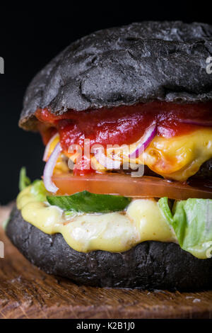 Fresh tasty burger on black background. Homemade hamburger with beef, onion, tomato, lettuce and cheese with ingredients - Stock Photo
