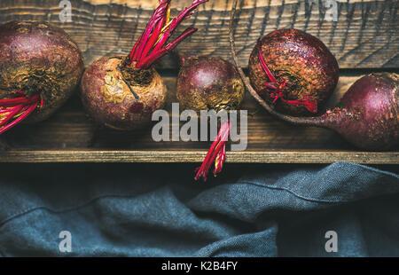 Raw organic purple beetroots in wooden box - Stock Photo