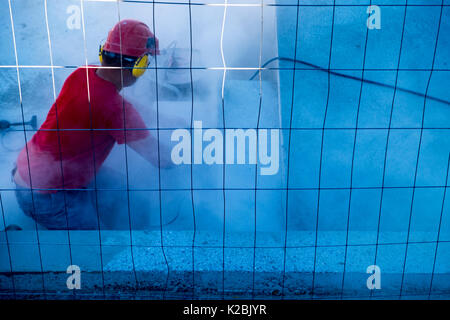 Construction worker wearing safety helmet and headphones uses a sander to sand the floor of a swimming pool - Stock Photo