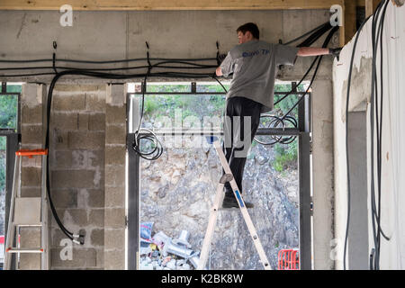 Electrician on a ladder works to install electrical cables in a new home under construction in the south of France - Stock Photo
