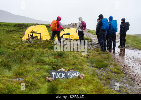 Hikers in pouring rain by Tuck Shop tents on West Highland Way trail path highest point & Hikers hiking by Tuck Shop tents on West Highland Way trail path ...